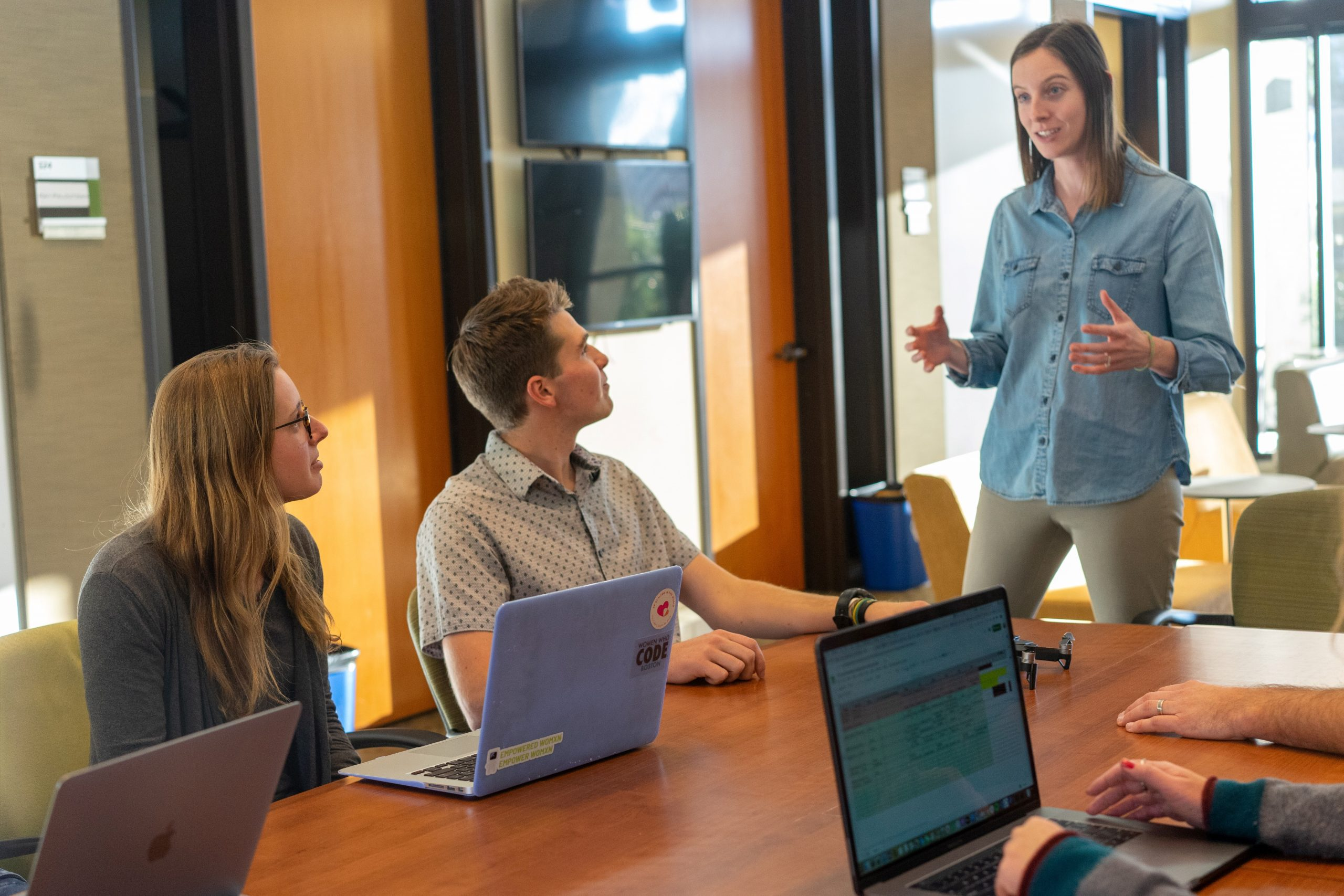 Tech business meeting being held in an office between three staff members