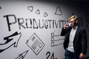 Image of productivity on the wall with a man on the phone